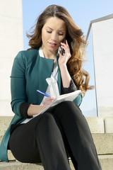 Geschäftsfrau mit Notizblock telefoniert mit smartphone