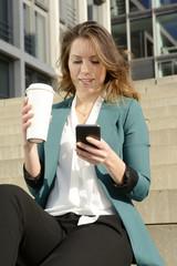 Geschäftsfrau mit smartphone und coffee to go