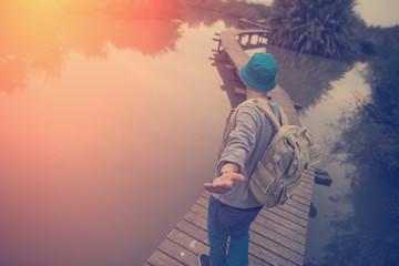 traveler with backpack walking over wooden bridge on lake