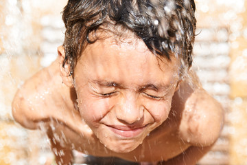 Child taking a refreshing shower during his summer vacation