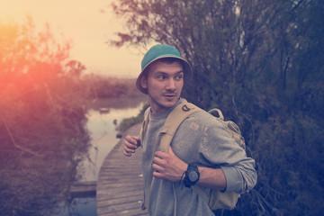 young traveler walking over wooden bridge in sunset