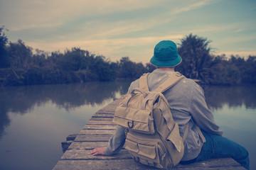 traveler sitting on the lake on the wooden bridge in sunset
