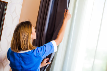 Hotel maid fixing the curtain