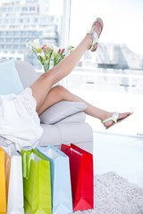 Brunette lying on the couch with shopping bags around her