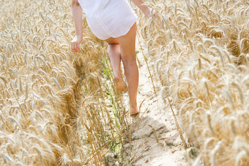 Girl walking barefoot on a field of rye