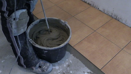 hand mix tile cement with machine tool at kitchen