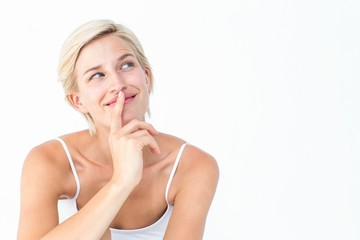 Beautiful blonde smiling with finger on mouth