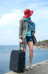 Girl in a red hat with a suitcase in front of the sea