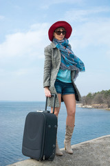 Girl in a red hat and with a suitcase in front of the sea