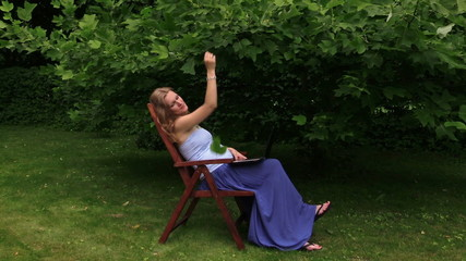 pregnant woman enjoy fresh air while work with laptop in garden