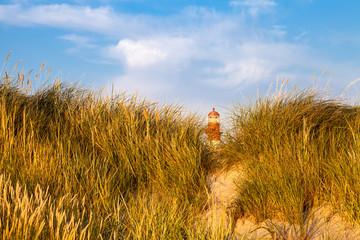 Lighthouse behind sand hill