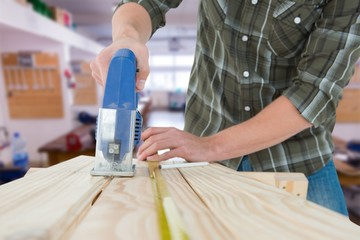Carpenter cutting wooden plank with electric saw