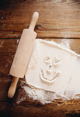 flour and rolling pin on wooden surface