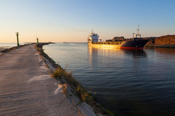 Freight ship in channel at sunset