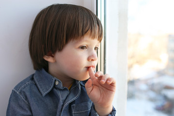 Little boy sits on sill and looks out of window in winter