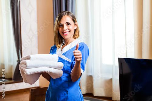 Szczęśliwy hotel pokojówka gospodarstwa ręczniki i pokazano kciuk w górę