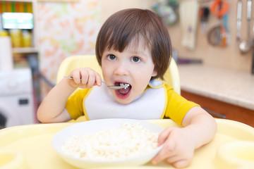 Little child eats quark with sour cream on kitchen