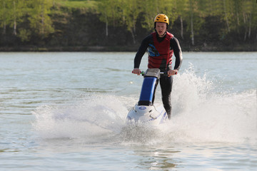 A guy stand on the jet ski.