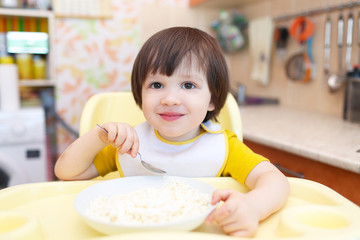 Smiling little boy eats quark with sour cream