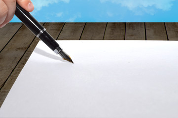 paper and pen on the wooden background