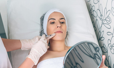 Pretty woman looking lips treatment in a mirror