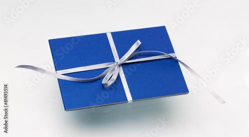Leinwanddruck Bild Karta podarunkowa w kolorze niebieskim i srebrną wstążką na białym tle.