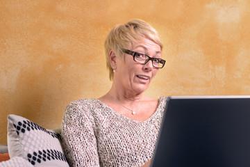 Ernste blonde Frau mittleren Alters mit einem Laptop Computer