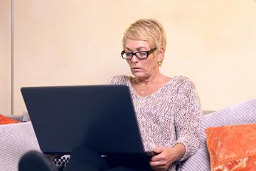 Ernste Frau mittleren Alters sitzt auf dem Sofa mit ihrem Laptop