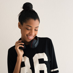 Happy brazilian girl portrait with headphones. Filtered image.
