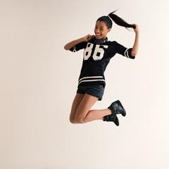Jumping brazilian girl full body portrait with headphones. Filte