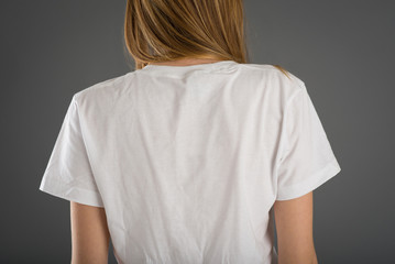 Back view of woman wearing white shirt against grey background.