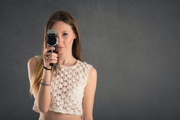 Blonde woman with vintage film camera close up against dark grun