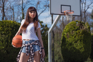 Young casual woman portrait holding basketball ball outdoors in