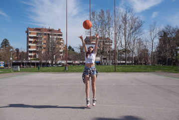 Young casual woman throwing basketball ball outdoors in a sunny