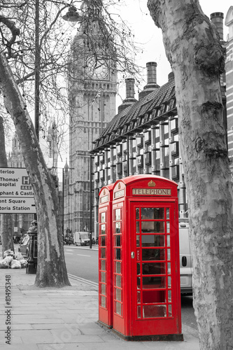 Classic red British telephone boxes with Big Bang in the backgro