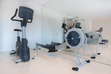 Cardio fitness equipment in the gym. Rowing and biking.