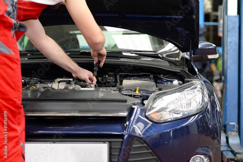 KFZ Mechaniker repariert Motor an einem Fahrzeug - 81496919