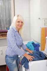 Junge Frau legt Wäsche zusammen