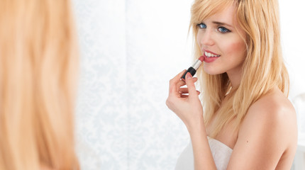 Smiling Blond Woman Applying Lipstick in Mirror