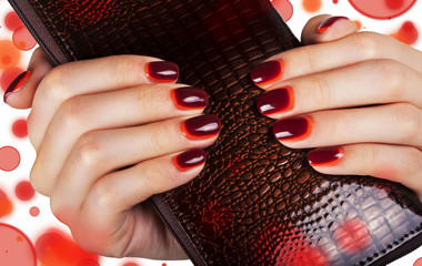 Women's manicure with maroon-red gradient polish on the nails.