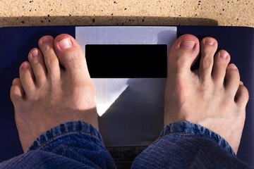 Man standing on weight scales in jeans