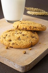 Chocolate chip cookies on a wooden board with milk