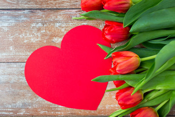 close up of red tulips and paper heart shape card