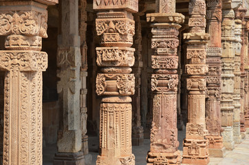 Columns with stone carving in courtyard of Quwwat-Ul-Islam mosqu
