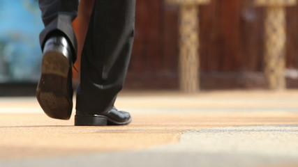 man in black trousers and shoes makes steps backwards