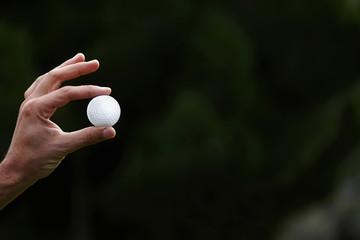 Male hand holding a golf ball on green nature background, player
