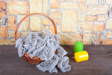 Knitted scarf in the basket and two color candles on wooden tabl