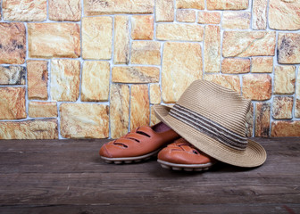 Straw hat and moccasins on a wooden table in front of a stone wa