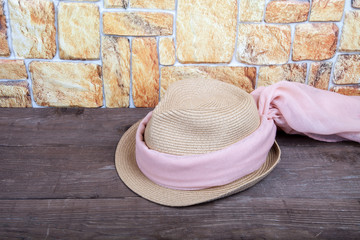 Straw hat and pink scarf on a wooden table in front of a stone w