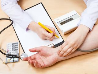 doctor measures blood pulse of patient